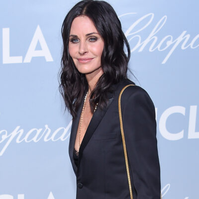 Courteney Cox in all black in front of a blue background.