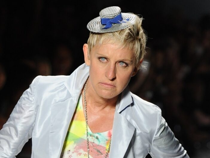 Ellen DeGeneres wears a silver suit and colorful top on the runway
