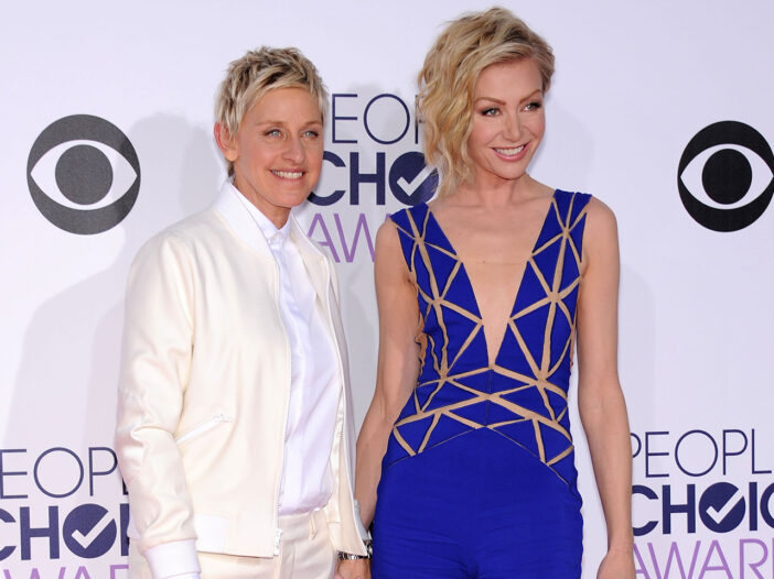 Ellen DeGeneres on the left in a white suit, standing with Portia De Rossi on the right in a very low cut blue dress.
