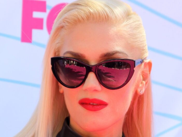 Gwen Stefani wears a black top and sunglasses on the red carpet