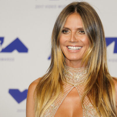 heidi Klum smiling in a gold dress