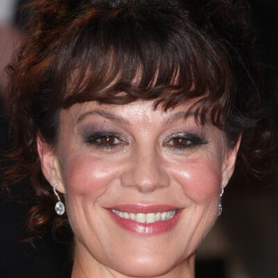 Helen McCrory, in an ivory gown, smiles as she walks the red carpet