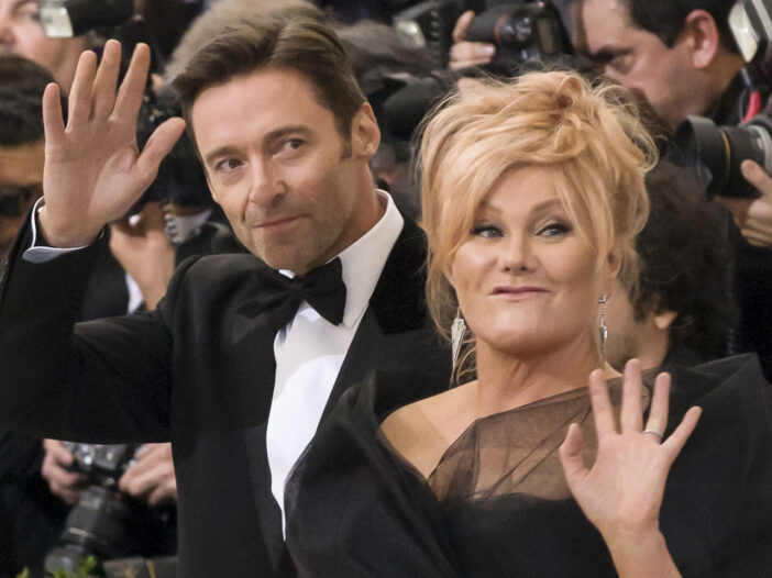Hugh Jackman and Deborra Lee Furness waving at a black tie event.