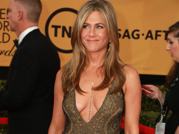 Jennifer Aniston in a low cut dress at a red carpet event.