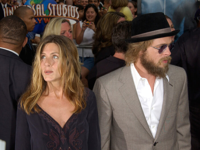 Jennifer Aniston looking off the left standing with Brad Pitt with a full beard and sunglasses, years ago.