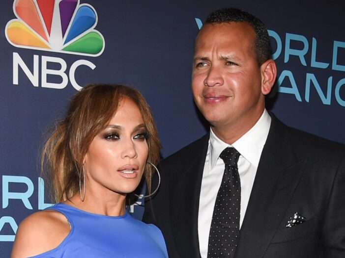 Jennifer Lopez, in a blue dress, poses with Alex Rodriguez, in a dark suit, on the red carpet