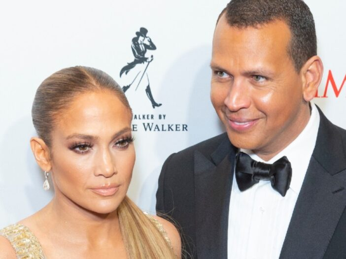 Jennifer Lopez, in a gold dress, stands with Alex Rodriguez, in a black tux, before a white background