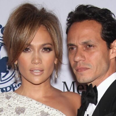 Jennifer Lopez wears a white dress and stands with Marc Anthony, who's dressed in a tuxedo