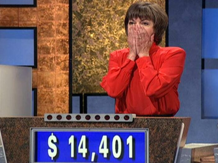 A contestant on Jeopardy! covers her face in surprise with both hands