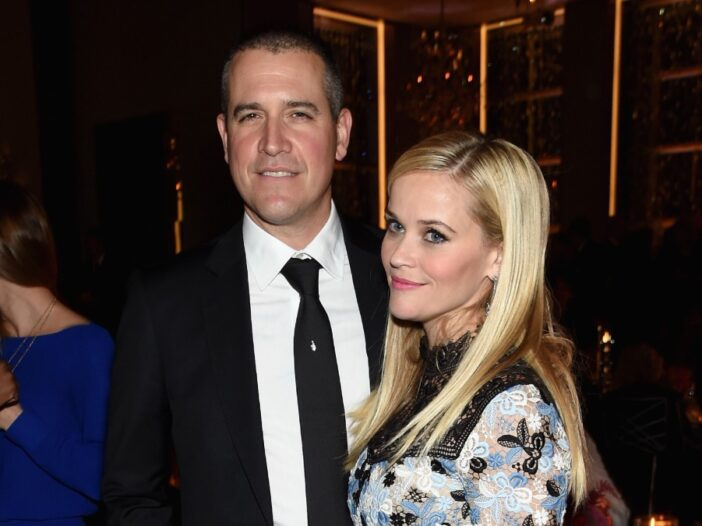 Jim Toth, wearing a black suit, poses with Reese Witherspoon, in a floral gown