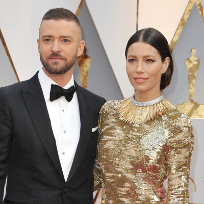 Justin Timberlake on the left, standing with Jessica Biel in a gold dress.