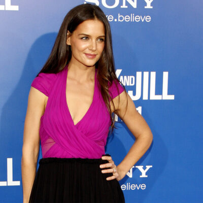 Katie Holmes in a pink top and black skirt with her hand on her hip
