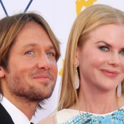 Keith Urban, in a black suit, stands with his wife Nicole Kidman, who wears a blue and white dreess