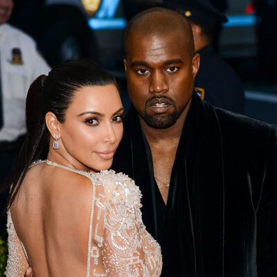 Kim Kardashian with her back to the camera, looking over her shoulder and standing next to Kanye West.