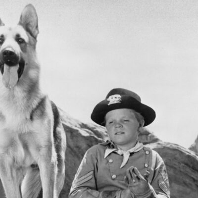 Lee Aaker wears his Rin Tin Tin costume and poses beside a German Shepherd