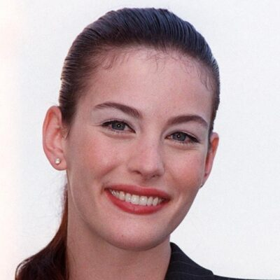 Liv Tyler smiles at the camera while wearing a black suit outdoors