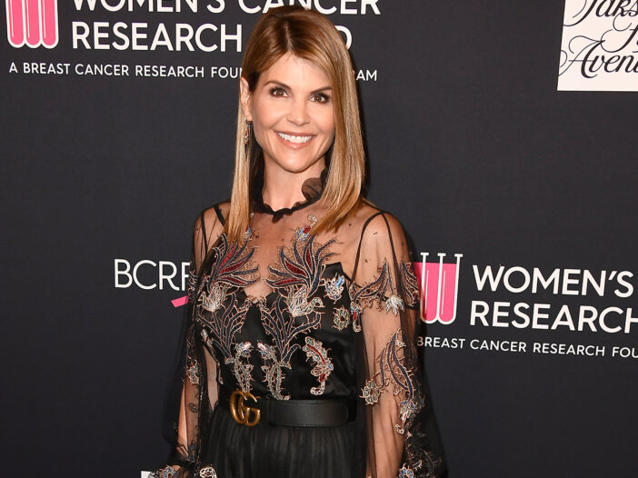 Lori Loughlin smiling in a black dress.