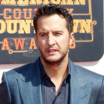 Luke Bryan wears a blue suit as he walks the red carpet at the American Country Countdown Awards
