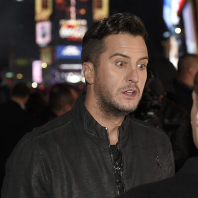 Luke Bryan, wearing a black jacket speaks to a man in Times Square
