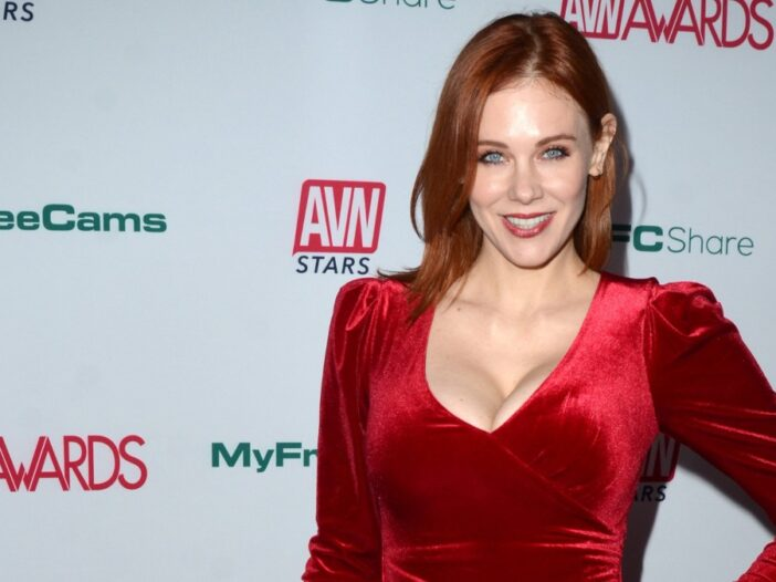 Maitland Ward wears a red dress with a plunging neckline against a white background