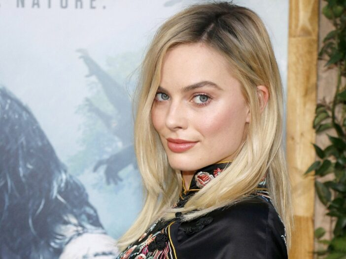 Margot Robbie wears a black dress and looks over her shoulder on the red carpet