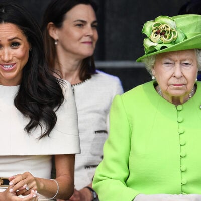 Meghan Markle making a funny face, sitting with Queen Elizabeth looking very serious.