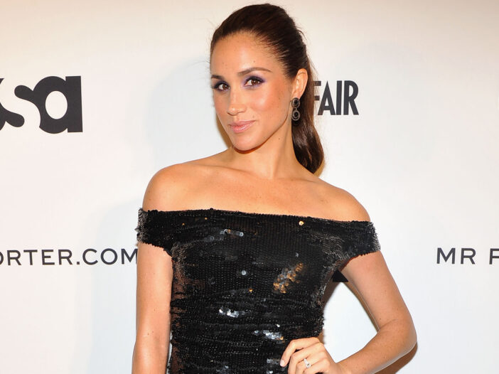 Meghan Markle looking sassy in a black dress at a red carpet event.