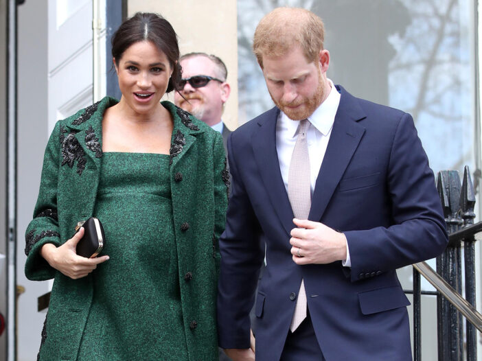 A pregnant Meghan Markle walking down some stairs with Prince Harry