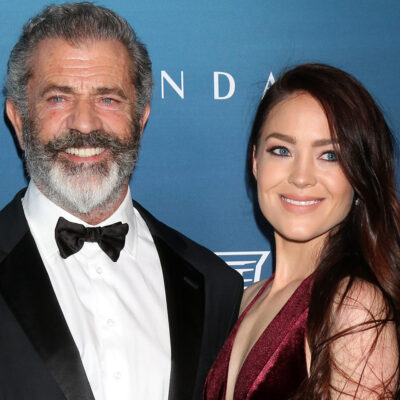 Mel Gibson Smiling in a tux, standing with Rosalind Ross in a red dress.