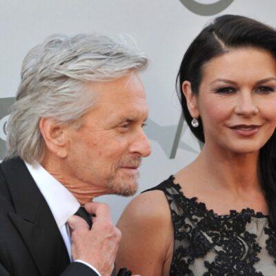 Michael Douglas adjusts his tie as he stands beside Catherine Zeta Jones
