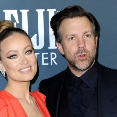 Olivia Wilde, in an orange dress, stands with Jason Sudeikis, in a black suit, on the red carpet