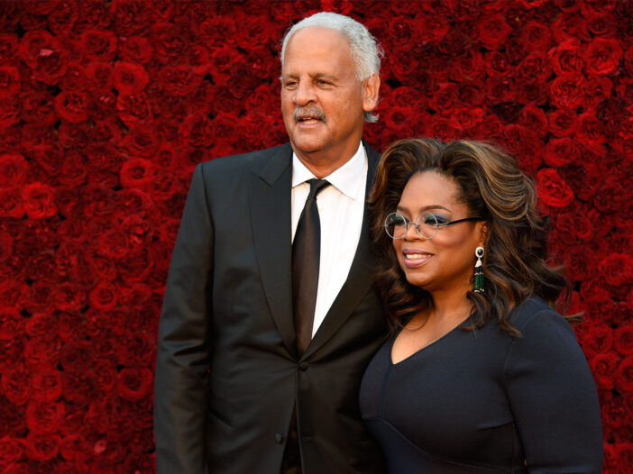 Stedman Graham on the left, Oprah Winfrey on the right, standing in front of a wall of roses.