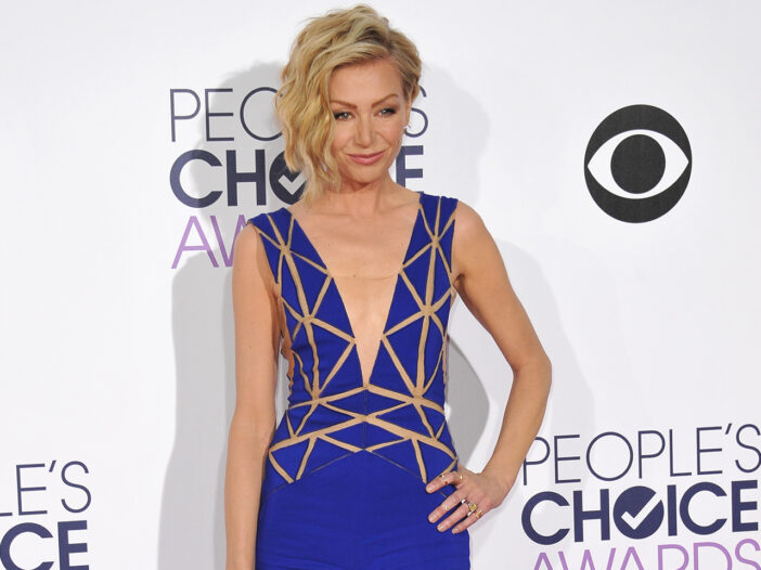 Portia de Rossi in a low-cut blue dress with her hand on her hip