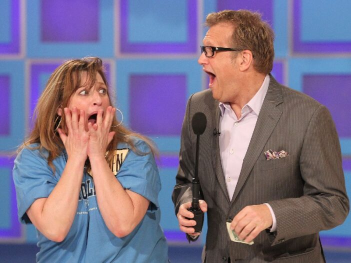 Drew Carey and a contestant on The Price Is Right make shocked faces at each other