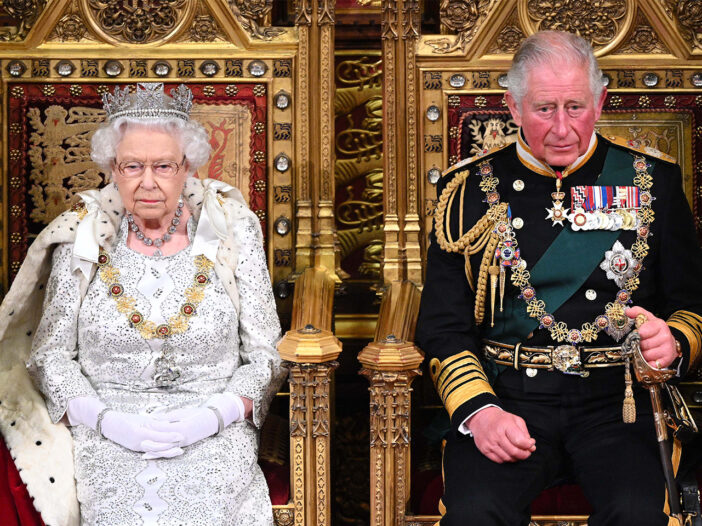 Queen Elizabeth sitting next to Prince Charles on thrones in the House Of Lords.