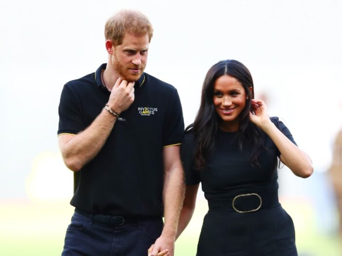 Prince Harry and Meghan Markle, both dressed in black, walk hand in hand