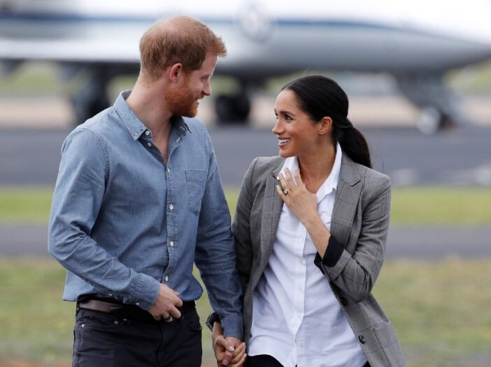 Prince Harry, in blue shirt, holds hands as he walks and talks with wife Meghan Markle, in a white shirt