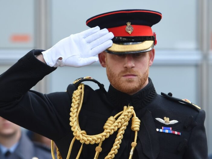 Prince Harry wears his military uniform and salutes something off camera