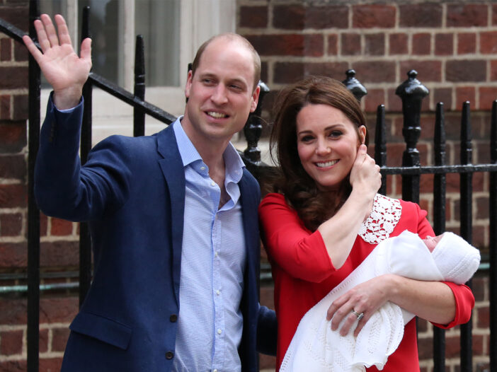 Prince William waving and standing next to Kate Middleton holding newborn Prince Louis on the steps of the hospital
