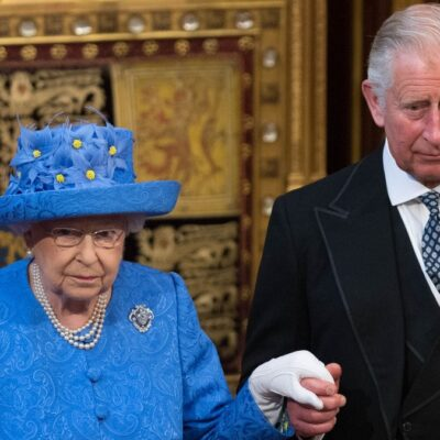 Queen Elizabeth, wearing all blue, walks through Parliament with Prince Charles, in a dark suit