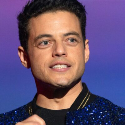 Rami Malek wears a sparkly blue jacket as he addresses an audience