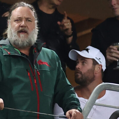 Russell Crowe with a long beard, cheering at a rugby match, with Chris Hemsworth looking to the side, behind Crowe.