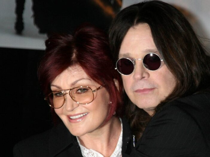 Sharon and Ozzy Osbourne, both dressed in black, cuddle up on the red carpet