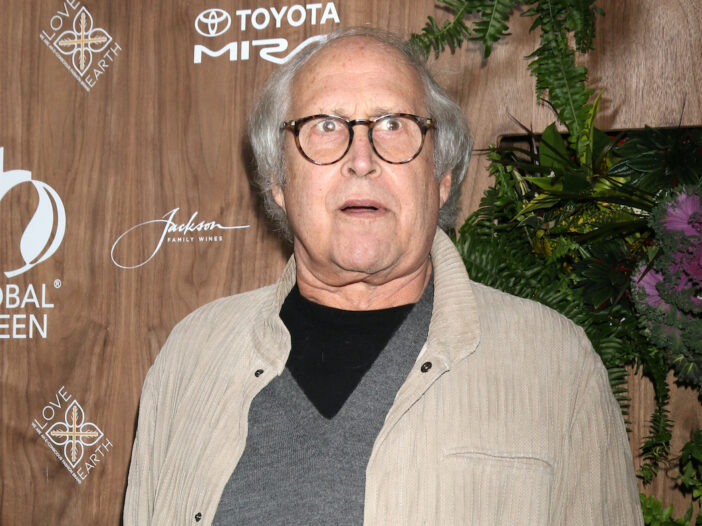 Chevy Chase in a tan coat and grey shirt