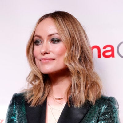 Olivia Wilde smiling in a green jacket