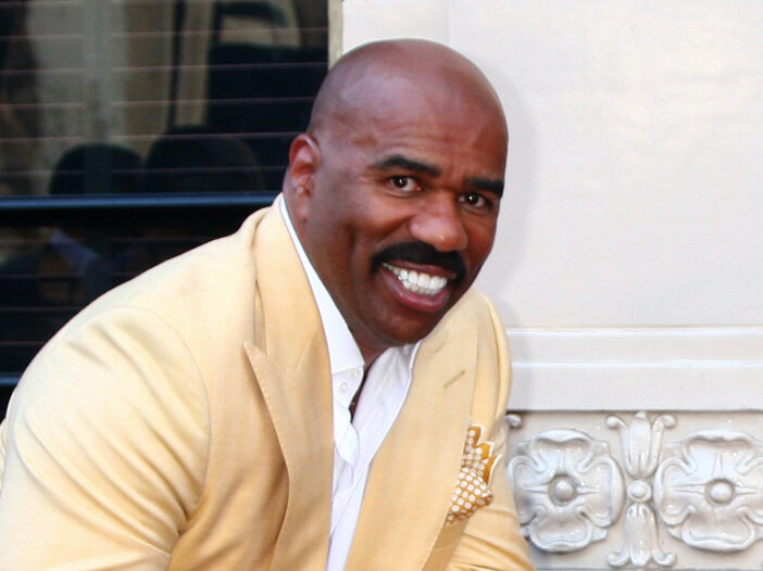Steve Harvey in a yellow suit smiling