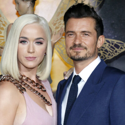 Katy Perry in a pink dress with Orlando Bloom in a suit
