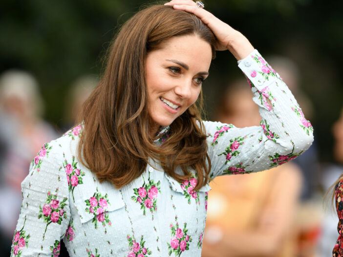 Kate Middleton with her hand on her head in a floral dress