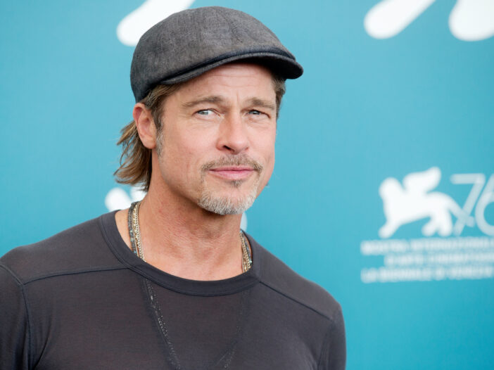 Brad Pitt in a grey sweater and hat