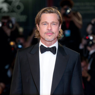 Brad Pitt in a tuxedo in front of photographers